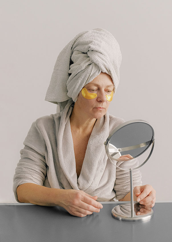 Woman with towel on head looking into a mirror by Anna Shvets