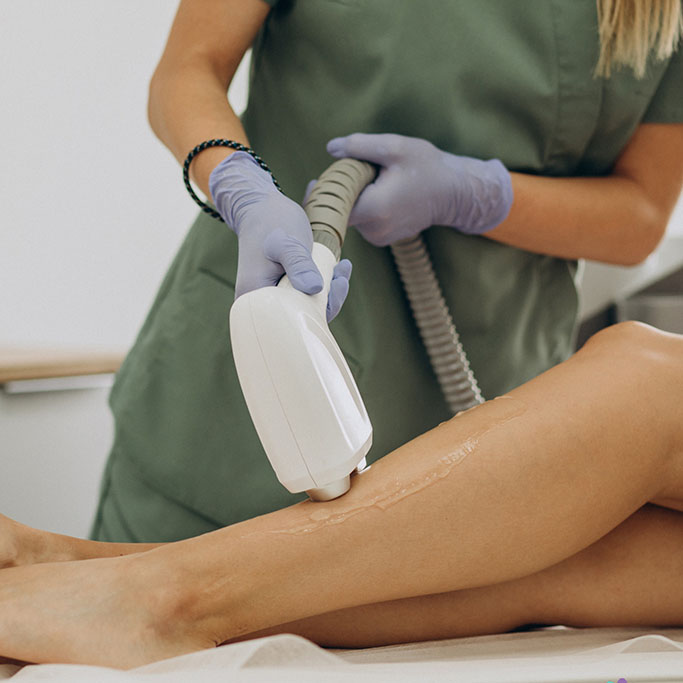 person operating laser treatment equipment on client