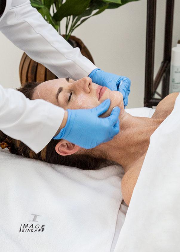 woman receiving image skin peel treatment