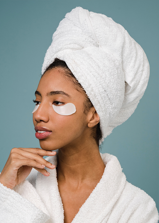 woman with towel on head with eyebag treatment