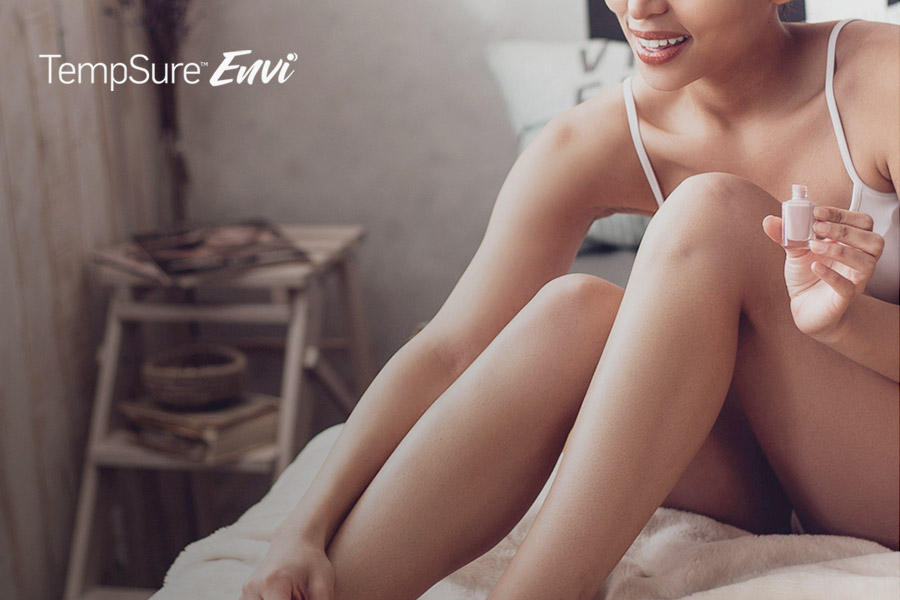 woman applying cosmetics while sitting in bed